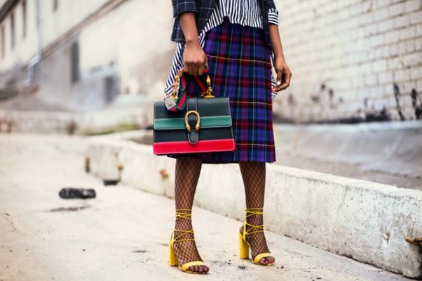 woman in blue and white stripped shirt and blue and red plaid skirt holding a red and green stripped purse. (Photo: Godisable Jacob/Pexels)
