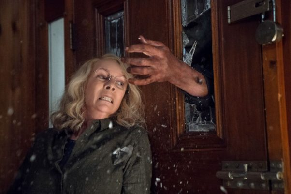 Jamie Lee Curtis leaning agains a door as a hand comes through the window in Halloween. (Photo: Universal Pictures)