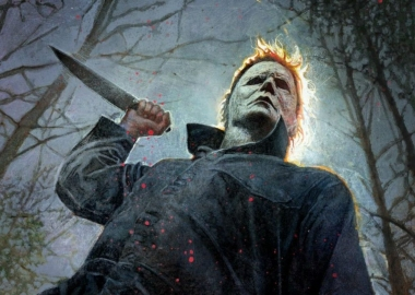 Mike Myers standing in front of trees with a knife raised in the air. (Photo: Universal Pictures)