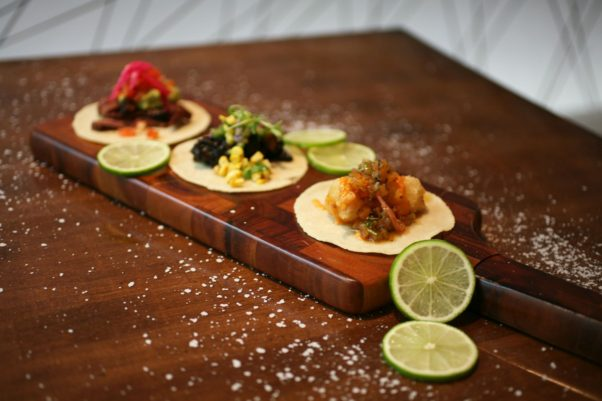 Three different kinds of tacos at MXDC on a cutting board with limes scattered around. (Photo: MXDC)