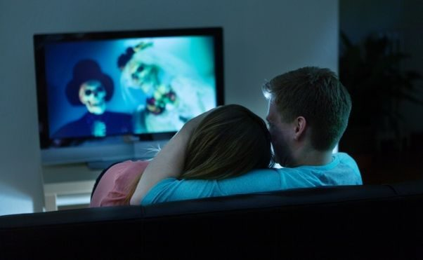 A couples watching a movies with skeltons dressed as a bride and groom at home. (Photo: MPTV Images)