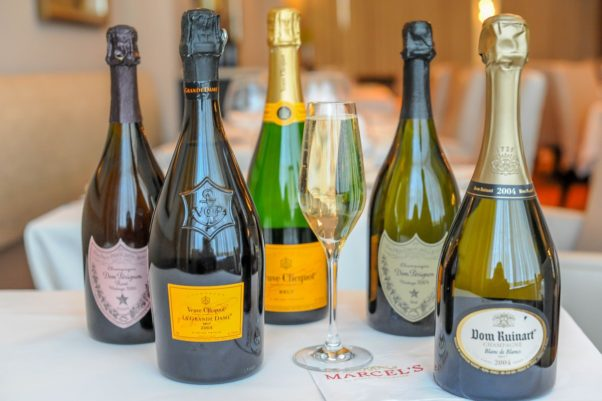 five bottles of differnt brands of champagne and a filled champagne flute in the middle. (Photo: Marcel's)