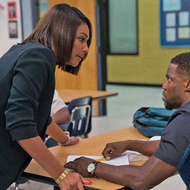 Teacher Tiffany Haddish standing over student Kevin Hart who is sitting at a desk in Night School. (Photo: Universal Pictures)