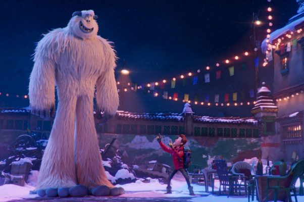 Migo the snowmonster stands stories above Percy in a town square in winter in Smallfoot. (Photo: Warner Bros. Pictures)