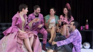 Five people sitting at a party in costumes from STC. (Photo: Shakespeare Theatre Co.)