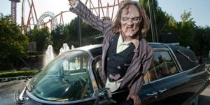 A zombie coming out the driver's side window of a car parked in front of a roller coaster. (Photo: Six Flags America)