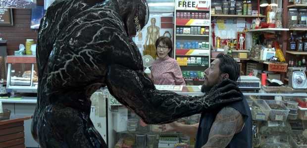Venom grabs a male Asian robber by the shoulder as the female Asian clerk looks on horrified. (Photo: Sony Pictures)