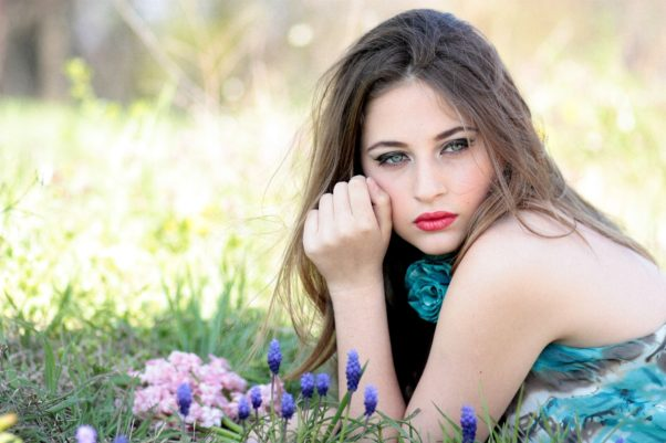 A beautiful woman lying in a field with purple flowers. (Photo; Pixabay)