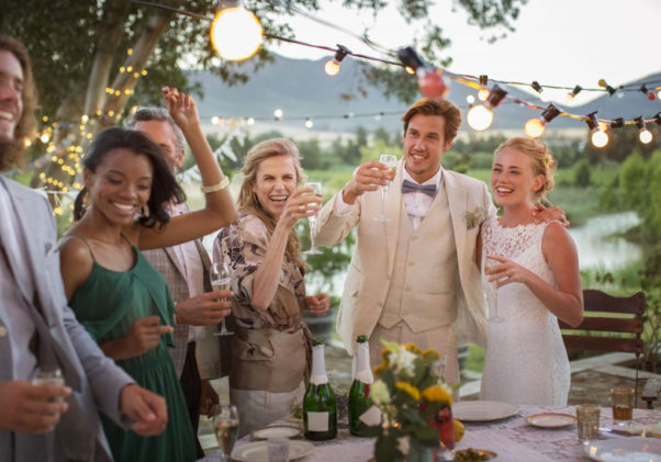 A bride and groom with guests standing around an outdoor table toasting. (Photo: Getty Images)