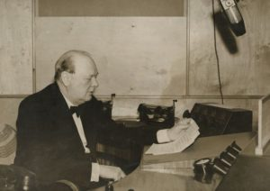Winston Churchill sitting at a desk in 1930 reading from paper and speaking into a radio microphone. (Photo: Churchill Archives Centre)