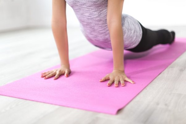 A woman on a pink yoga mat pushing her shoulders up with her arm with her legs on the ground. (Photo: Burst/Pexels)