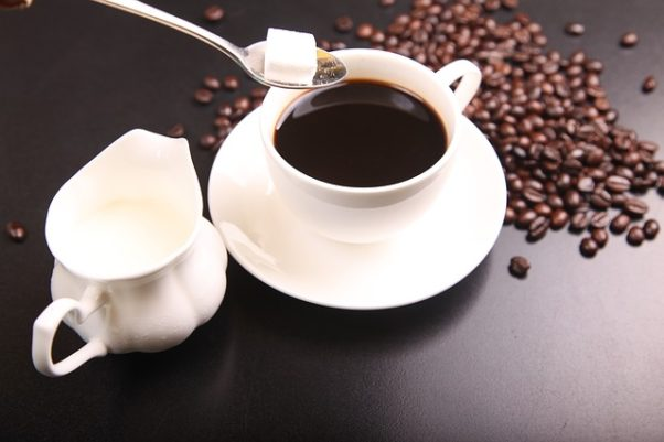 A cup of coffee with somone putting a sugar cube from a spoon into it with a cramer beside the cup and coffee beans on the table. (Photo: shixugang/Pixabay)