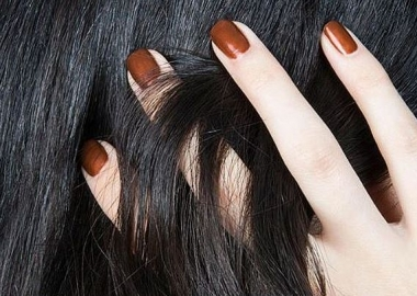A close up of a woman with running her hand through her black hair. The four fingers you can see are painted a copper color. (Photo: Narsissist/Instagram)