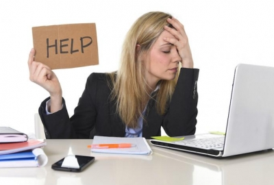 Woman sitting at computer with hand over face holding a sign that says help.