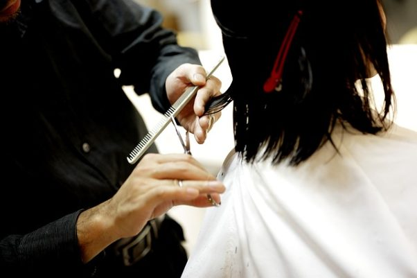 Closeup of a woman in a salon getting her hair cut by someone using comb and scissors. (Photo: kaleido-dp/Pixabay)