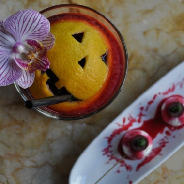 Cocktail with a jack-o-lantern face carved into an orange peel floating in itand two vampire bites pintxos that look like bloody skewered eyeballs on a plate beside it. (Photo: Estadio)