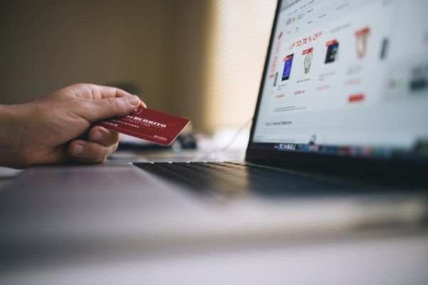 a hand holding a credit card beside a laptop on an ebay page. (Photo: Negative Space/Pexels)