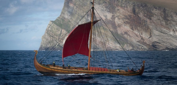 The Viking ship Draken Harald Hårfagre sailing past a cliff. (Photo Viking Nilsson):