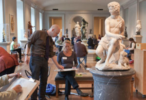 A woman sketcing at statue at the NGA while an instructor gives tips. (Photo: National Gallery of Art)