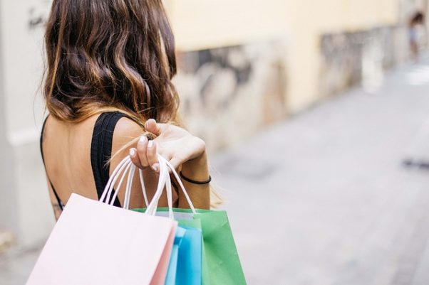 A woman carrying four shopping bags over her shoulder. (Photo: gonghuimin468/Pixabay)
