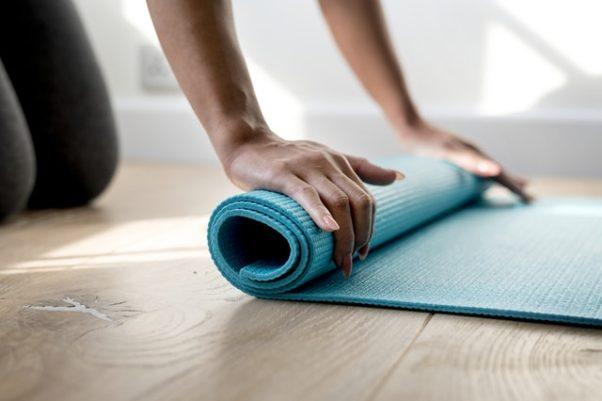 A kneeling woman rolluing up a green yoga mat. (Photo: Rawpixel/Pexels)