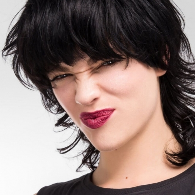A dark haired woman with her face scrunched up wearing burgundy lipstick. (Photo: The Organic Skin Co.)