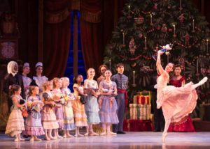 A girl holding a nutcracker dancing in front of a Christms tree while other children and servants watch. (Photo: The Washington Ballet)