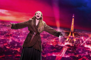 Anastasia singing and dancing in front of a back drop of Paris with the Eiffel Tower. (Photo: Johan Persson)