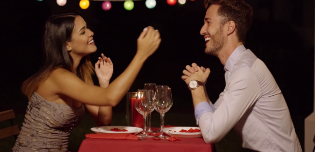 Couple eating dinner and smiling while casually dressed for a night time dinner-date. (Photo: Vidoeblocks)