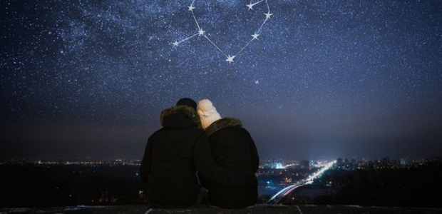 A man and woman sitting outside under stars forming a heart with an arrow through it. (Photo: 123RF.com)