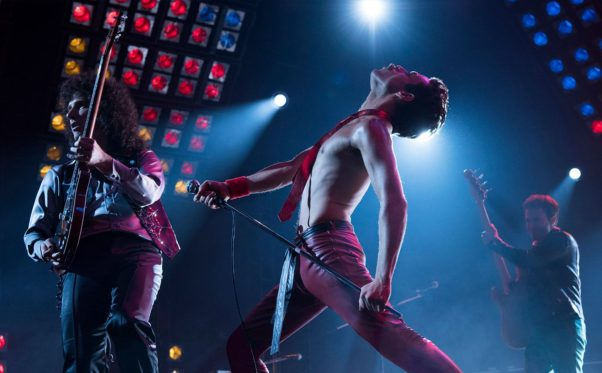 Freddy Mercury shirtless but wearing a tie performing on stage with the other members of Queen. (Photo: 20th Century Fox)