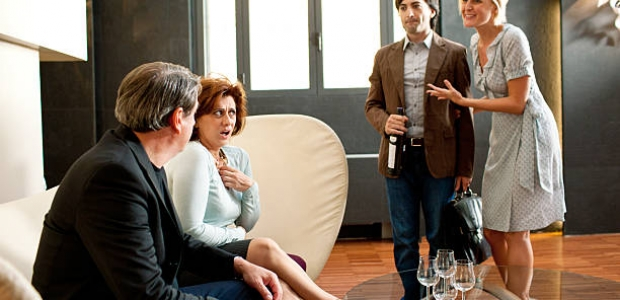 A woman introducing her boyfriend to her parents, who are sitting on a couch. (Photo: iStock)