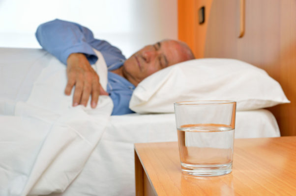 Senior man lying on bed with glass of mineral water on the nightstand. (Photo: Getty Images)
