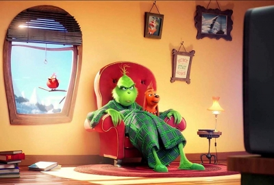 The Grinch sitting in a chair in his living room watching TV with Max the dog on his lap. (Photo: Universial Pictures)