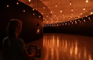 A woman holds a sensor under a ceiling of hundreds of clear, incandescent light bulbs that pulse with her heartbeat. (Photo: Hirshhorn Museum)