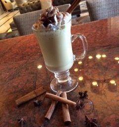 Clear glass mug filled with spiced nog cocktails topped with whipped cream and ground cinnamon with cinnamon stick and anise laying beside the glass. (Photo: Jardenea Lounge)