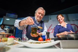 Jacques Pepin pous dressing over a dish as his daughter looks on. (Photo: Metro Cooking D.C.)