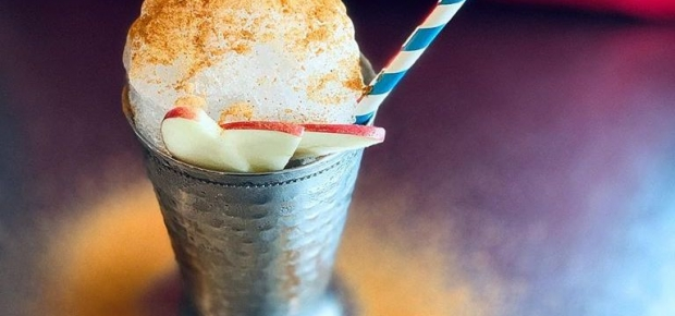 A drink in a metal cup topped with foam, baking spices and apple slices with a blue and white straw. (Photo: The Royal)