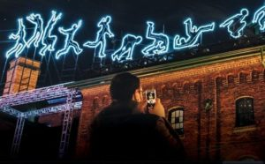 A man taking a photo of outlines of a person running and falling made from neon lights along the top of a building. (Photo: Georgetown BID)