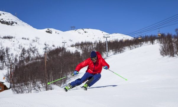 photo of a person in red jacket and blue pants downhill skiing in snow. (Photo: Terje Sollie/Pexels)