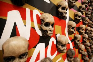 artwork of skulls on a black, red, brown and white background. (Photo: Libby Weiler)