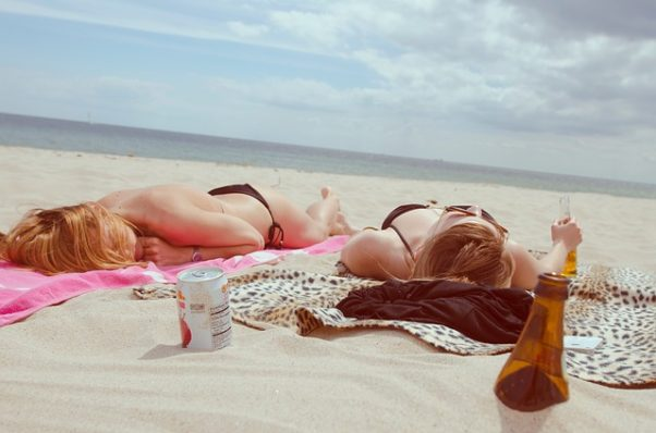 Two women lying on the beach in bikinis with beer and other items sitting around them. (Photo: Free-Photos/Pixabay)