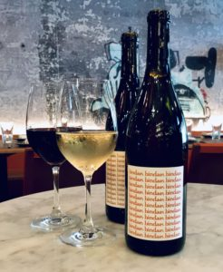Two bottles of Cuvée Bindaas beside a glass of red wine and a glass of white wine in a Bindaas restaurant. (Photo: Knightsbirdge Restaurant Group)
