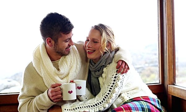 man and woman in white sweaters and scarves cudding in a ski lodge with cups of coffee and a blanket. (Photo: Deposit Photo)