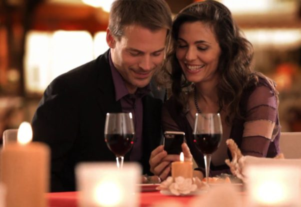 Middle-aged couple eating dinner at a restaurant looking at a smart phone. (Photo: Videoblocks)
