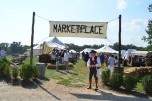 A man dressed in Colonial garb sanding under a sign that says Marketplace in front of tents of artisans selling their wares. (Photo: Kathy Reesey)