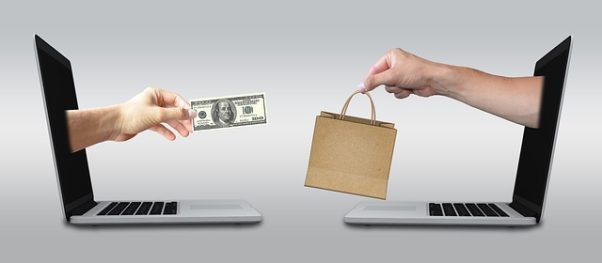 One hand coming out of a laptop screen holding a $100 bill with another hand coming out of another compuer screen holding a paper shopping bag. (Photo: Mediamodifier/Pixabay)