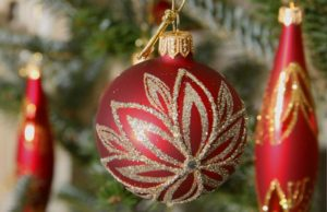 Three red and gold glass ornaments hanging on a Christmas tree. (Photo: Glassor)