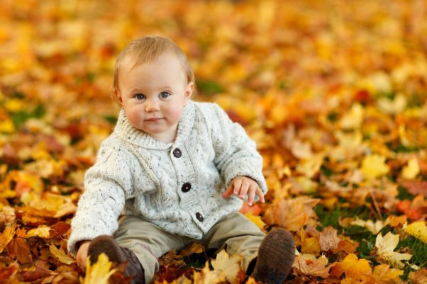 A baby stting in leave wearing a gray cardigan sweater. (Photo: Pexels)