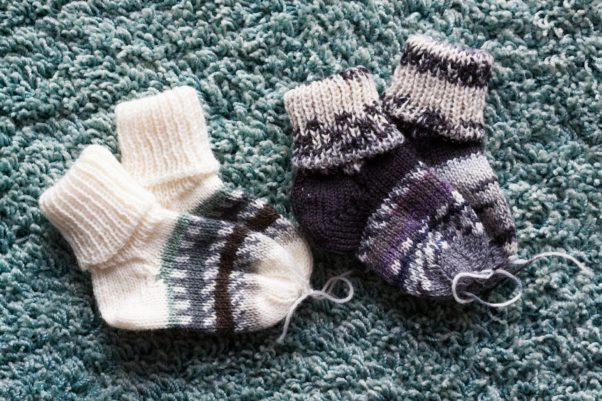 Two pairs of knit gray and white baby socks lying on knit material. (Photo: Pixabay)